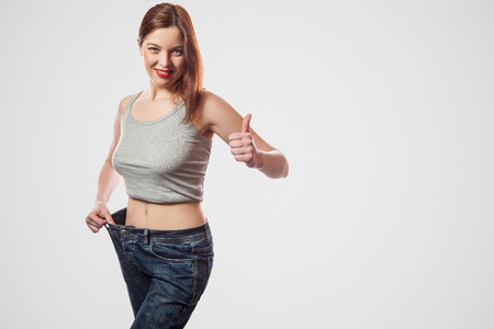 portrait of happy beautiful slim waist of young woman standing in big jeans and gray top showing successful weight loss, indoor, studio shot, isolated on light gray background, diet concept. 写真素材