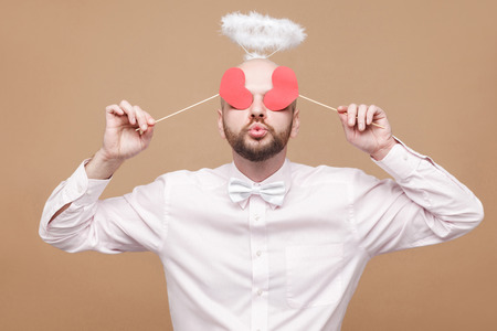 Happy handsome middle aged bald bearded angel in shirt and white halo on head standing and closing the eyes with two heart stickers and air kissing. studio shot, isolated on light brown background.