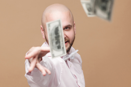 Portrait of happy handsome middle aged bald bearded businessman in white shirt standing, throw out money and looking at camera with proud rich face. studio shot, isolated on light brown background.