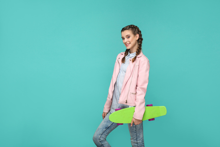 happy beautiful girl in casual style, pigtail hair and pink jacket, standing and holding skateboard and looking at camera with toothy smile, Indoor isolated, studio shot on blue or green background Stock Photo