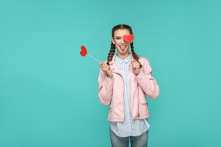 Funny beautiful girl in casual style, pigtail hairstyle and pink jacket, standing and holding red heart stickers and looking at camera with tongue out, Indoor, isolated on blue or green background Stock Photo