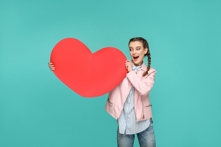 Amazed beautiful girl in casual style, pigtail hairs and jacket, standing and holding and looking at big red heart shape with surprised face. indoor, studio shot isolated on blue or green background