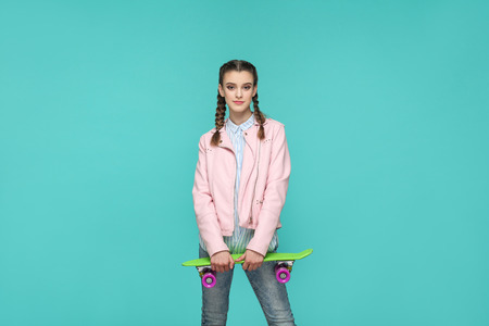 hipster beautiful girl in casual style, pigtail hairstyle and pink jacket, standing and holding skateboard and looking at camera and smiling, Indoor isolated, studio shot on blue or green background