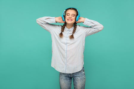 Happy satisfied girl in striped blue shirt and pigtail hairstyle, standing listening favorite music with headphones, closed eyes and toothy smiling, Indoor studio shot, isolated on green background