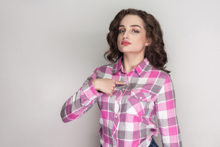 Satisfied proud beautiful girl with pink checkered shirt, curly hairstyle and makeup standing and looking at camera, pointing herself with serious face. indoor studio shot, isolated on gray background Stock Photo