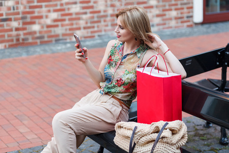 Profile side view of beautiful young woman dressed in tropical shirt and siting on black bench in the street and looking at the smart phone after shopping with red big bag. Outdoor shot.
