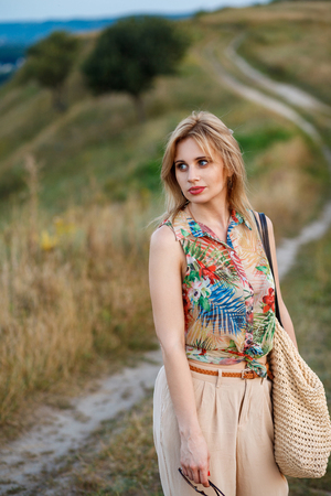 Young beautiful thoughtful woman in tropical blouse and beige galligaskins with wicked bag standing on village road and looking aside. Outdoor shot, nature shot, sunny day.