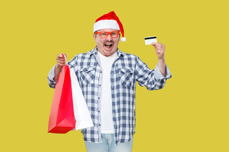 Suprised open mouth middle aged man in casual style and new yar red hat, standing, holding shopping bags and credit card with amazed face, looking at camera. Studio shot, isolated on yellow background