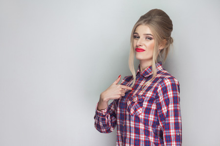 Satisfied proud beautiful blonde girl in pink checkered shirt and collected updo hairstyle standing and looking at camera, pointing herself with serious face. studio shot, isolated on gray background