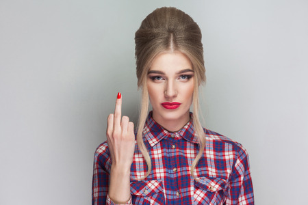 angry beautiful blonde girl in pink checkered shirt and collected updo hairstyle standing, looking at camera and showing middle finger with poker face. indoor studio shot. isolated on gray background 스톡 콘텐츠