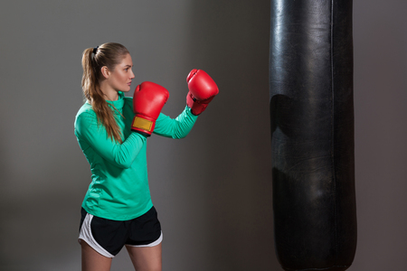 Side view of athlete woman in green long sleeve and black shorts standing in attack position, ready to fight punching bag in boxing red gloves. Indoor studio shot, isolated on dark grey background. Stock Photo