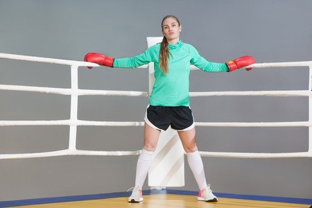 Confident beautiful young athlete woman with collected hair standing in the corner of boxing ring in boxing red gloves and looking at camera. Indoor studio shot. on gray background.