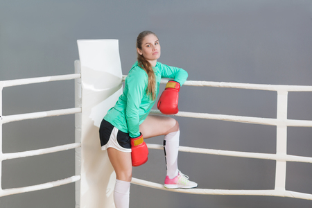 Beautiful athletic young woman with collected hair wearing in green long sleeve and red gloves standing, leaning on near boxing ring and looking at camera. indoor studio shot. on gray background.