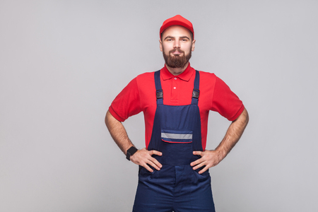 Portrait of young confident repairman with beard in blue overall, red t-shirt and cap standing and holding hands on waist with smile, indoor, studio shot, isolated on gray background, copy space.