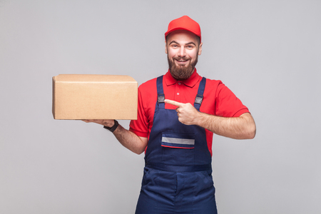 Young cheerful logistic delivery man with beard in blue uniform and red t-shirt standing, holding and pointing finger to cardboard box on grey background. Indoor,studio shot,isolated, copy space