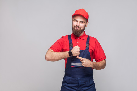 We do ontime. Young confident handyman with beard in blue overall and red t-shirt standing and showing time on his wrist watch with smile. Grey background, indoor, studio shot, isolated Banque d'images - 108524820