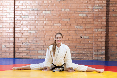Beautiful athletic karate woman in white kimono with black belt stretching in twine and looking at camera. Japanese martial arts concept. Indoor, studio shot, brown bricked wall background