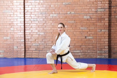 Beautiful athletic karate woman in white kimono with black belt in fighting stance looking at camera. Japanese martial arts concept. Indoor, studio shot, brown bricked wall background