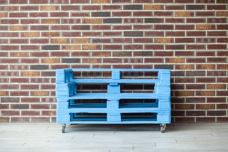 Blue shipping pallets for sitting with weels on brick wall background.