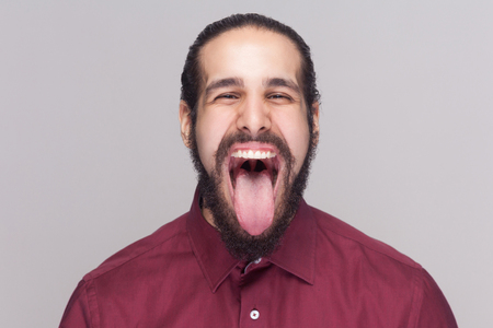 Portrait of funny crazy handsome man with beard in red shirt looking at camera with big open mouth and tongue out and screaming or shouting. indoor studio shot, isolated on gray background.