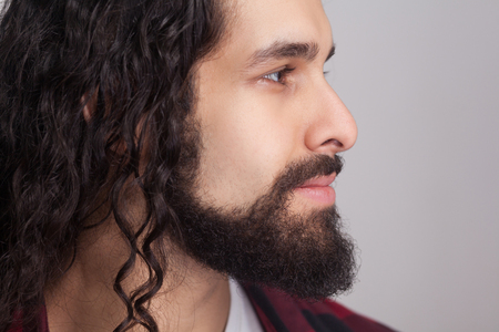 Closeup profile side view of handsome confident man with black long curly hair and beard, looking away with smile. male healthcare and beauty concept. indoor studio shot, isolated on gray background.