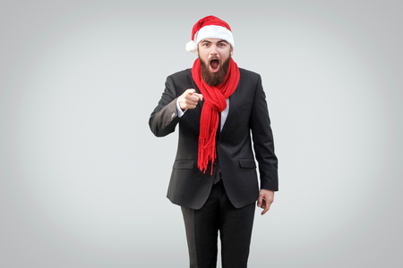 wow, is it you are? Surprised handsome bearded businessman in black classic suit , christmas cup and red scarf shocked, looking and pointing at camera. Indoor, studio shot, isolated on gray background