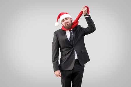 Thoughts of suicide. Unhappy businessman bankrot and dont have time to until christmas. looking at camera and holding his scarf with sad emotion, indoor studio shot isolated on gray background