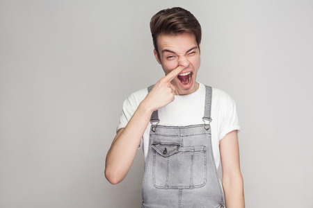Portrait of funny crazy young brunette man in casual style with denim overalls standing and looking at camera with open mouth and finger in nose . indoor studio shot, isolated on gray background. Imagens