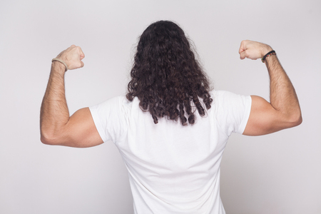 Back side of strong bodybuilder man in white t-shirt with long wavy hair, standing and posing with raised arms showing his biceps and muscular body. indoor studio shot, isolated on white background. Stock Photo