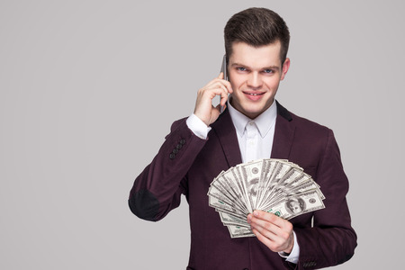 Portrait of prosperous attractive young businessman in classic violet coat standing, showing fan of money and make arrangements on mobile phone. Indoor studio shot, isolated on gray background. Imagens