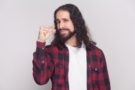 Give me a few more please. handsome man with beard and black long curly hair in casual style, checkered red shirt standing and pleading a few more time. indoor studio shot, isolated on grey background Banco de Imagens