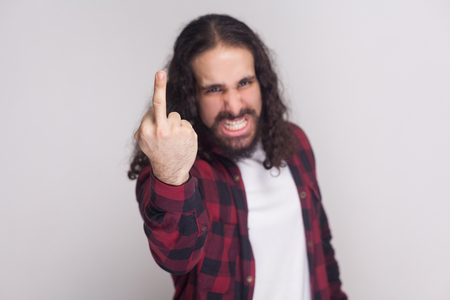 Portrait of angry handsome man with beard and black long curly hair in casual checkered red shirt standing looking at camera and showing middle finger. indoor studio shot, isolated on grey background Imagens