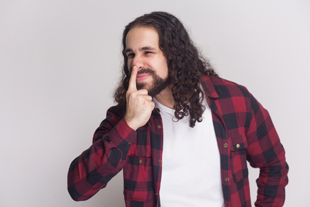 You are liar. angry man with beard and black long curly hair in casual style, checkered red shirt standing, looking away and showing lie gesture. indoor studio shot, isolated on grey background.