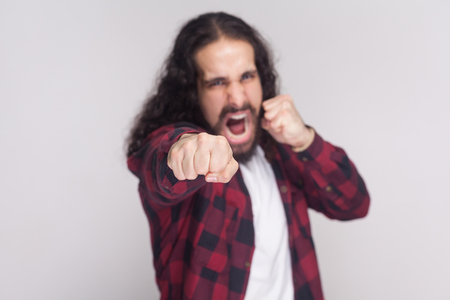 Angry screaming man with beard and black long curly hair in casual checkered red shirt standing, looking at camera and attacking with boxing fists . indoor studio shot, isolated on grey background