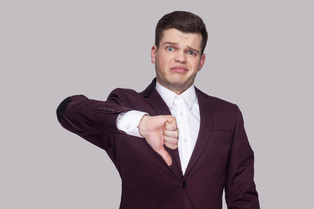Portrait of handsome confused young man in violet suit and white shirt, standing, looking at camera with thumbs down and unsatisfied face. indoor studio shot, isolated on grey background. Stockfoto