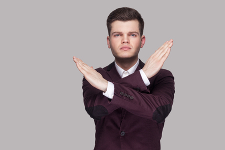 There is no way. Portrait of serious handsome young man in violet suit and white shirt, standing, looking at camera and crossed hands. indoor studio shot, isolated on grey background.