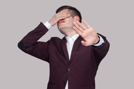 I dont want to see this. Portrait of confused young man in violet suit and white shirt, standing, closed his eyes with hands and showing stop gesture. indoor studio shot, isolated on grey background.
