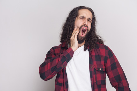 Sad screaming handsome man with beard and black long curly hair in casual style, checkered red shirt standing with painful tooth and feeling toothache. indoor studio shot, isolated on grey background.