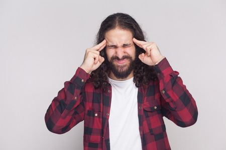 confused handsome man with beard and black long curly hair in casual style, checkered red shirt standing holding his head and closed eyes with headache. indoor studio shot, isolated on grey background