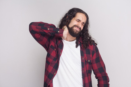 Portrait of sad handsome man with beard and black long curly hair in casual style, checkered red shirt standing and holding his painful neck with closed eyes. studio shot, isolated on grey background.