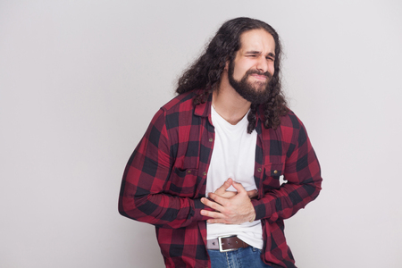 Portrait of sick handsome man with beard and black long curly hair in casual style, checkered red shirt standing holding his stomach with pain. indoor studio shot, isolated on grey background. Stockfoto
