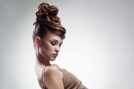 side view of attractive brunette woman with stylish hairdo and makeup posing on isolated grey background. indoor, studio shot on copy space.