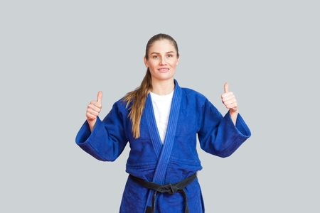 Positive athletic karate woman in blue kimono with black belt standing, showing thumbs up and looking at camera with toothy smile. Japanese martial arts concept. Indoor, studio shot, gray background
