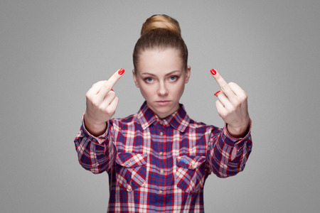angry beautiful blonde girl in pink checkered shirt and collected bun hairstyle standing, looking at camera and showing middle finger with poker face. indoor studio shot. isolated on gray background 免版税图像