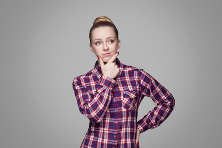 Confused beautiful blonde girl in red, pink checkered shirt, collected bun hairstyle, makeup standing and looking away, touching her face and thinking. indoor studio shot. isolated on gray background
