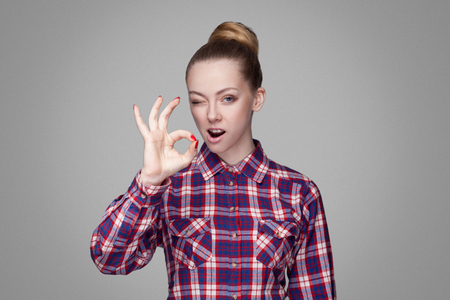 funny kissing beautiful girl with pink checkered shirt, collected bun hairstyle and makeup standing and showing Ok sign and looking at camera with wink. indoor shot, isolated on gray background. Stock Photo