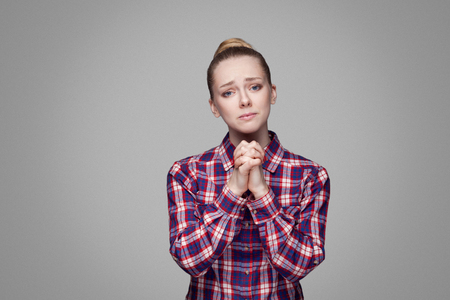 Please help me. beautiful blonde girl in red, pink checkered shirt, collected bun hairstyle standing and looking at camera with palm hands and begging. indoor studio shot. isolated on gray background