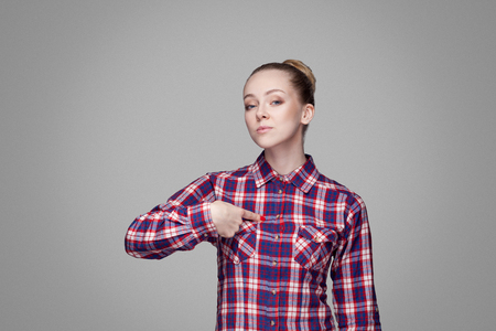 Satisfied proud beautiful blonde girl in pink checkered shirt and collected bun hairstyle standing and looking at camera, pointing herself with serious face. studio shot, isolated on gray background Stock Photo