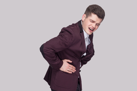 Profile side view portrait of unhappy handsome young man in violet suit and white shirt, standing and holding his painful stomach and feeling pain. indoor studio shot, isolated on grey background.
