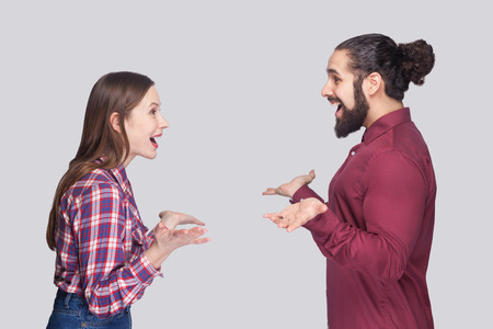 Profile side view portrait of funny surprised bearded man with bun hair and woman in casual style standing, looking at each other with amazed face. indoor studio shot, isolated on gray background Banque d'images